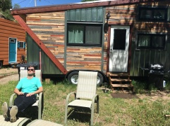 Man relaxing in chair outside of tiny house