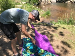 Man Laying Out Picnic Blanket near Creek
