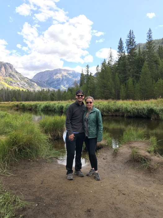 Husband and wife taking a picture in front of the creek and mountains