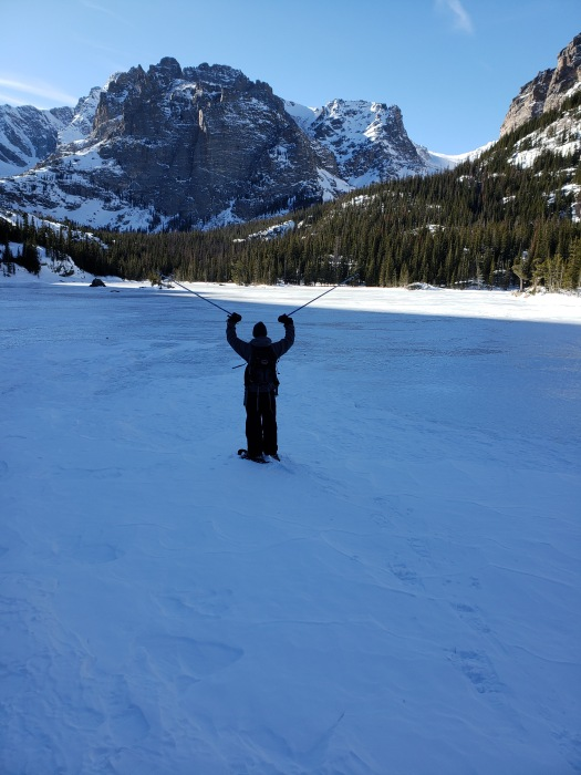 Man celebrating on frozen lake with mountains in background