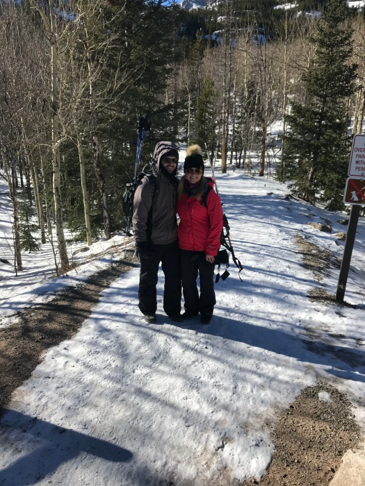Husband and wife taking picture on snow covered trail