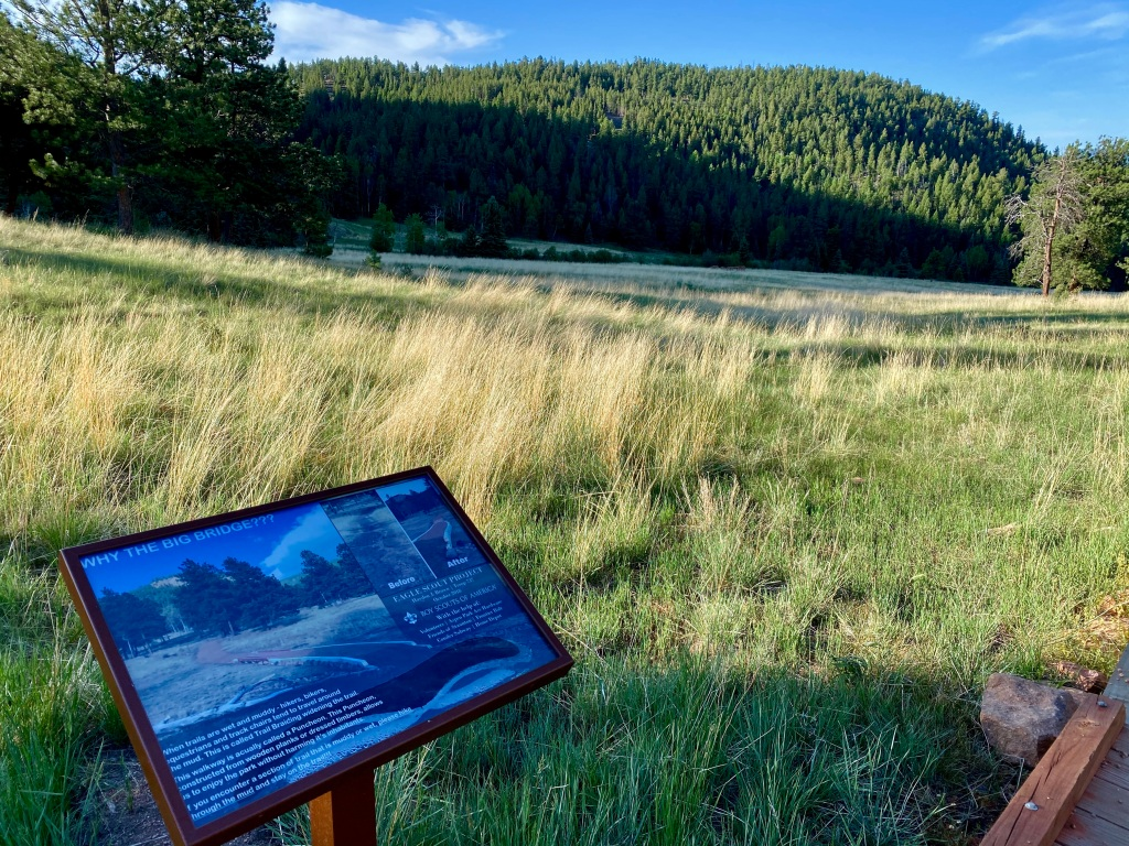 View of the meadow and a sign describing the bridge just crossed