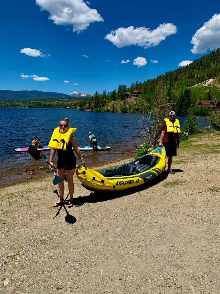 Husband and wife holding inflatable kayak with lake next to them