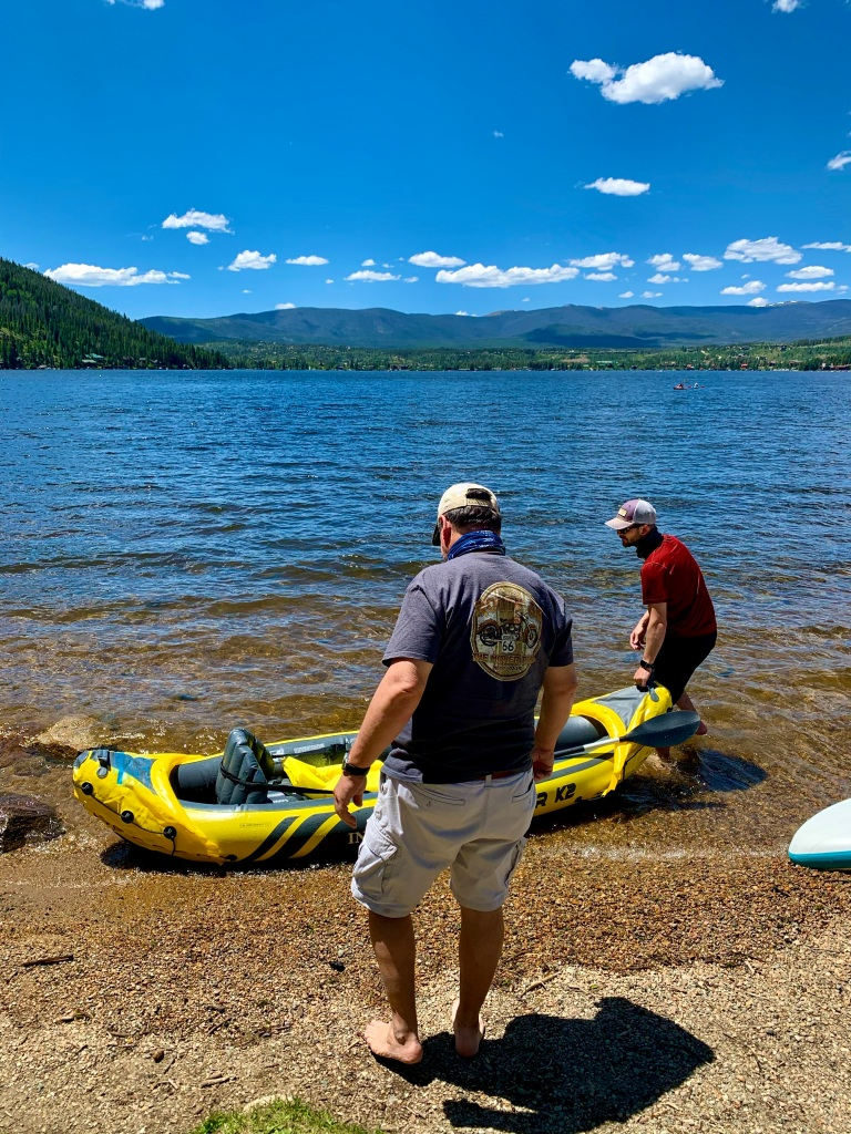 Father and son with kayak getting into the lake