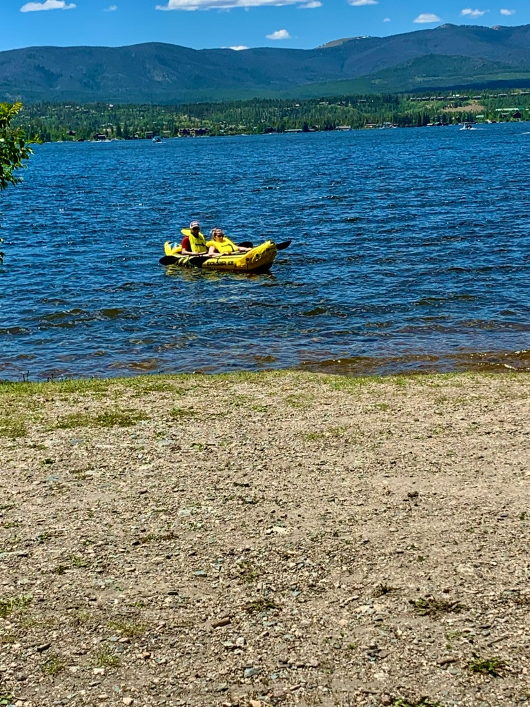 Husband and wife in kayak on lake with mountains behind