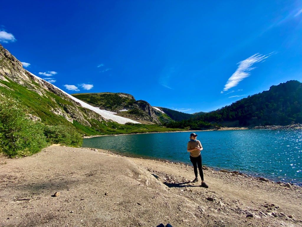 Woman standing along edge of mountain lake