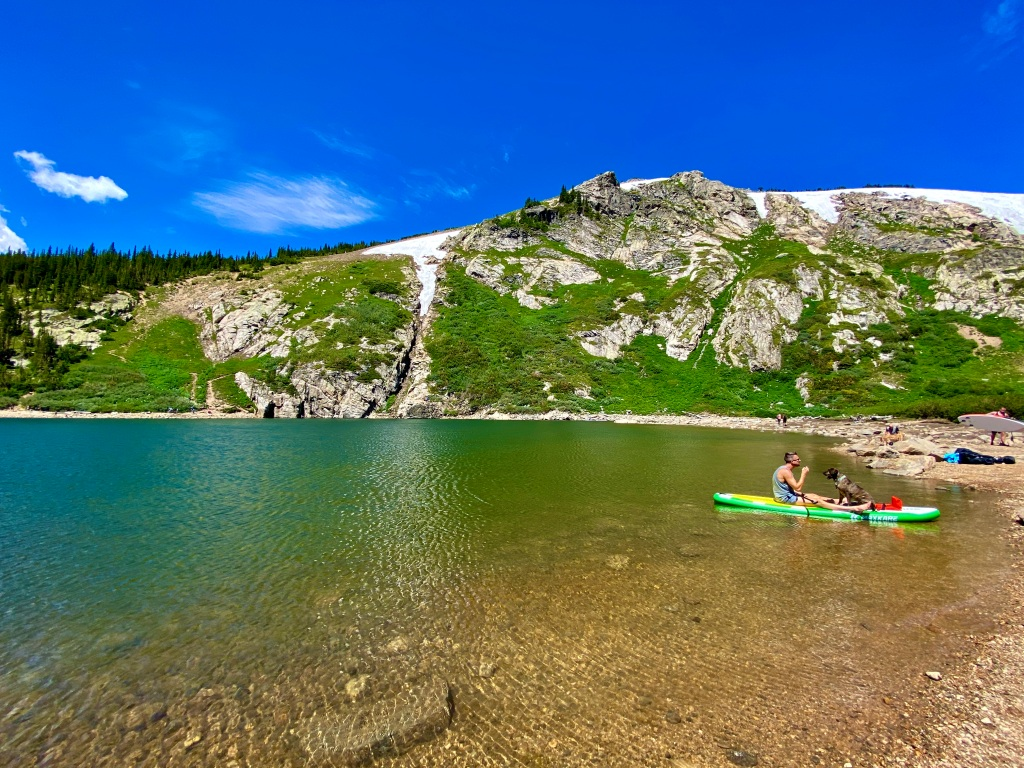 Man sitting on paddle board with his dog on the shore of the mountain lake