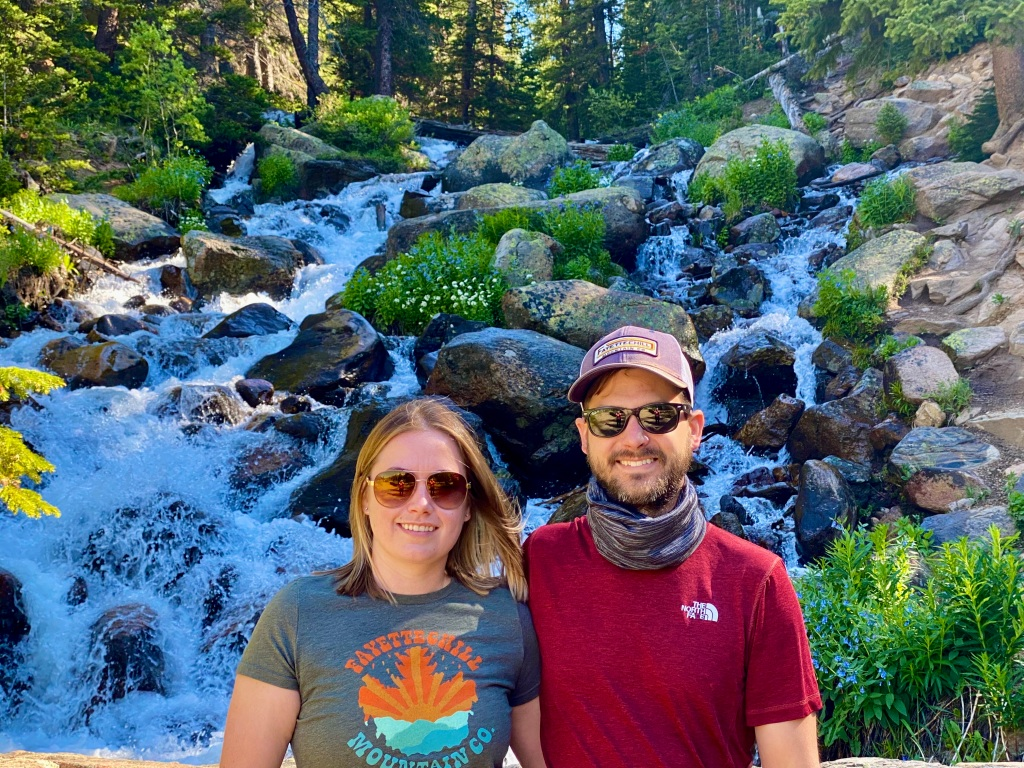 Husband and wife standing in front of waterfall taking picture