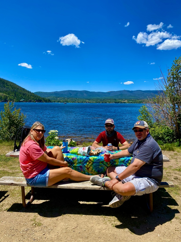 Family sitting around picnic table with drinks and snacks, and lake in the background