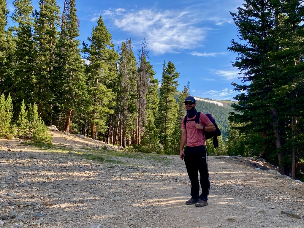 Man with backpack smiling for picture with pine trees in background