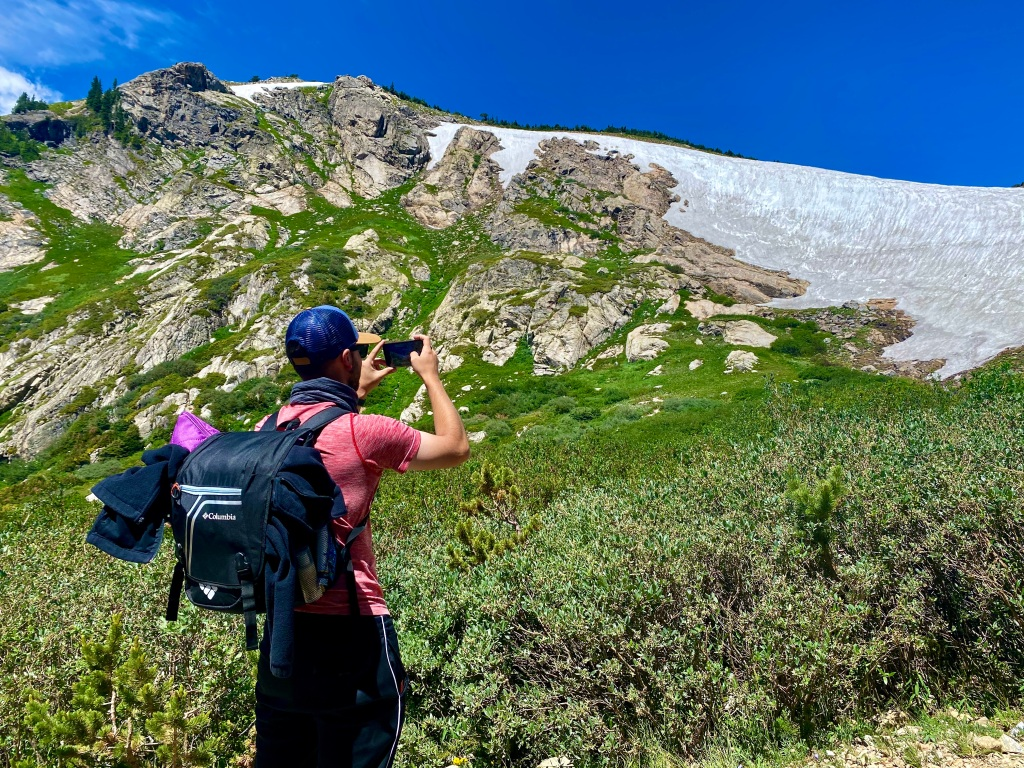 Man taking picture of the glacier with backpack on