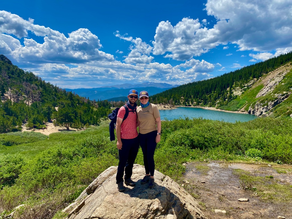 Husband and wife take picture on rock with mountain lake in the background.